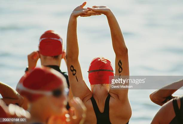 triathletes stretching before swimming leg of race (rear view) - triathlon stock pictures, royalty-free photos & images