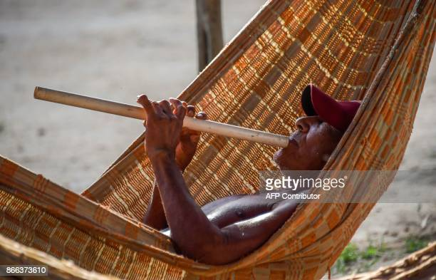 Tribal chieftain Tzako Waiapi plays the flute in the morning at the Manilha village in Waiapi indigenous reserve in Amapa state in Brazil on October...