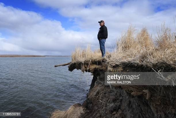 Tribal elder Warren Jones stands on a site threatened by climate change erosion caused by melting permafrost tundra and the disappearance of sea ice...