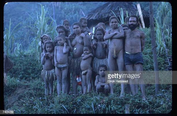 A tribal family stands in front of a hut June 6 1980 in Irian Jaya Indonesia Government attempts to move Indonesians into less populated areas of the...
