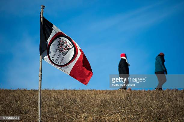 A tribal flag flaps in the wind as water protectors walk down Highway 1806 at Oceti Sakowin Camp on the Standing Rock Sioux Reservation in Canon Ball...