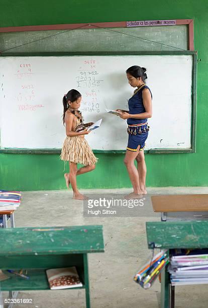 tribal girl (6-7) and her teacher, amazonian rainforest, ecuador - hugh sitton bildbanksfoton och bilder