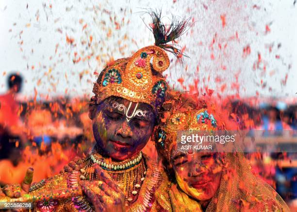 Tribal Indian students from the Kalinga Institute of Social Science dressed as Lord Krishna and Radha are smeared with with coloured powder and...