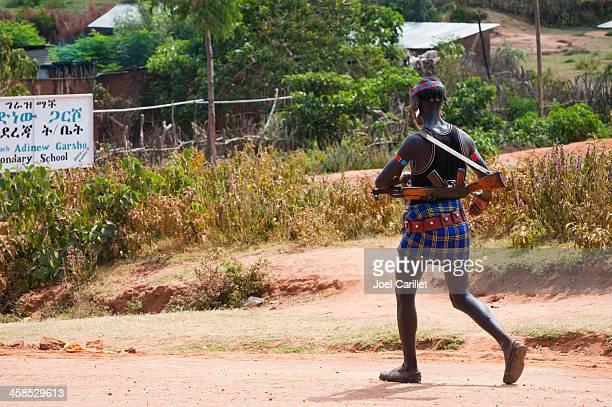 Tribal man walking with rifle