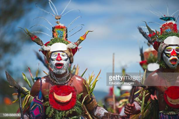 Tribal performers at Singsing Mt Hagen Show in Western Highlands Papua New Guinea with Papuan Lorikeet birds and King of Saxony plumes in head dress