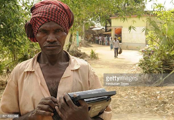 A tribal Som Mardi listening to election updates through radio at the Tribal Village Murgabuni Bolpur on April 17 2016 in Birbhum District India...