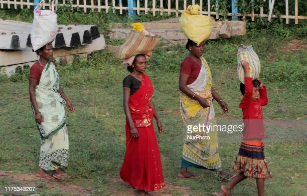 Tribal villagers balanced their luggage atop their head as they walks in the railway track to board in a pssenger train at Ranchi in the eastern...