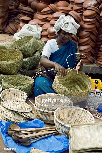 A tribal woman making a basket Kerala India