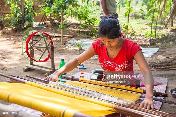 Tribal woman weaving cloths on a hand loom