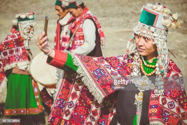 Tribal young woman of Kinnaur taking selfie in smartphone.