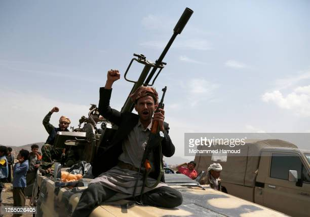 Tribesmen loyal to the Houthi group ride a truck mounted with a machine gun during an armed tribal gathering on July 08, 2020 on the outskirts of...