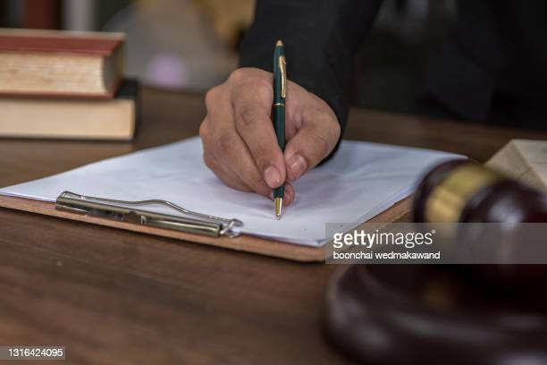 tribunal attorney lawyer working with documents and wooden judge gavel on table in courtroom. - supreme court justice stock pictures, royalty-free photos & images