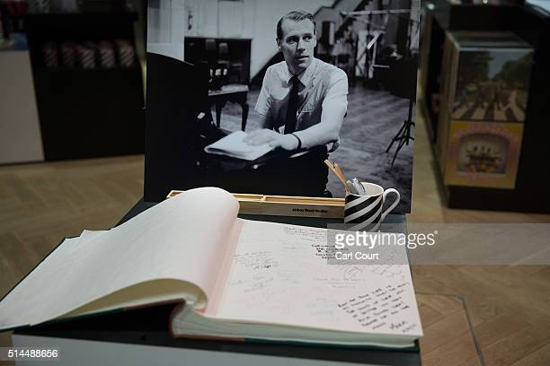 A tribute book is placed beneath a photograph of Beatles producer George Martin in the shop of Abbey Road Studios on March 9 2016 in London England...