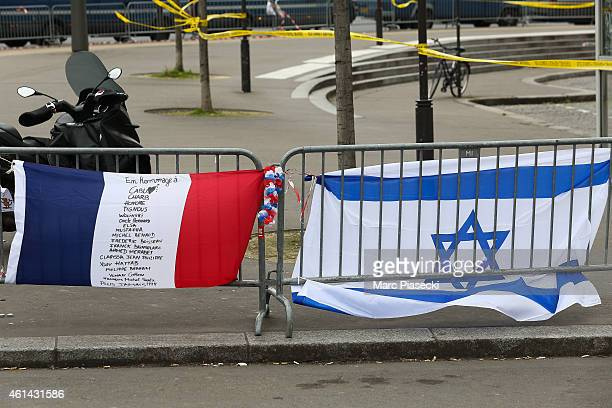 Tribute flags are left in the area while Benjamin Netanyahu Prime Minister of Israel pays his respects at the Hyper Cacher following the recent...