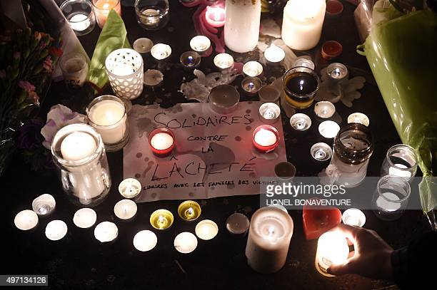 """Tribute message which translates as """"Solidarity against cowardice, solidarity with the families of victims"""" sits amongst candles at the entrance to..."""