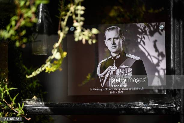Tribute photographs are seen in the window of a pub near Windsor Castle following the death of Prince Philip, on April 09, 2021 in Windsor, United...