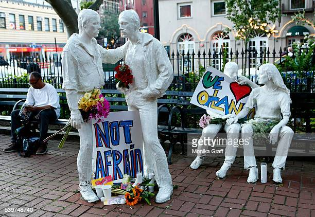 Tribute signs are placed on statues depicting homosexual couples in a park near the Stonewall Inn where a vigil was held following the massacre that...
