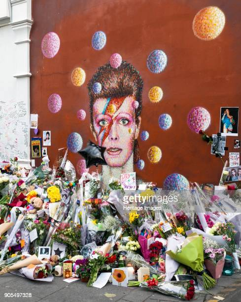 Tribute to David Bowie Tunstall Road Brixton London January 2016 Flowers and tributes surround the mural of pop star David Bowie after his death The...