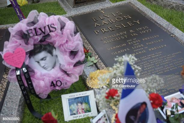 Tributes and momentoes are seen next to the grave marker for Elvis Presley in the Meditation Garden where he is buried alongside his parents and...
