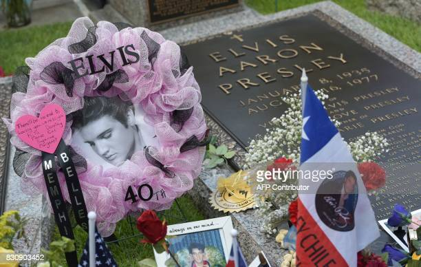 Tributes and momentoes are seen next to the marker for Elvis Presley in the Meditation Garden where he is buried alongside his parents and...