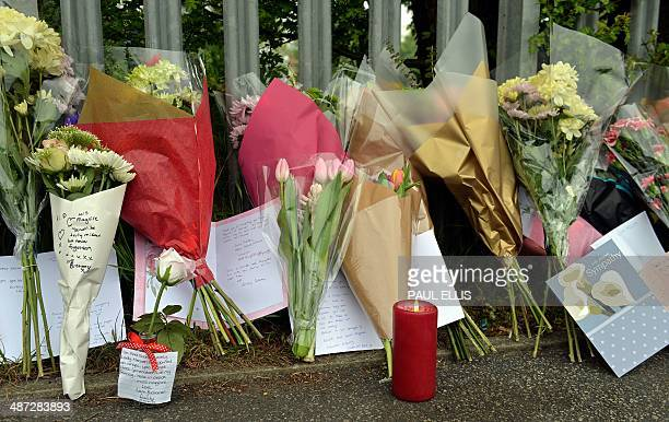 Tributes are pictured outside Corpus Christi Catholic College in Leeds, northern England on April 29 following the fatal stabbing of Spanish teacher...