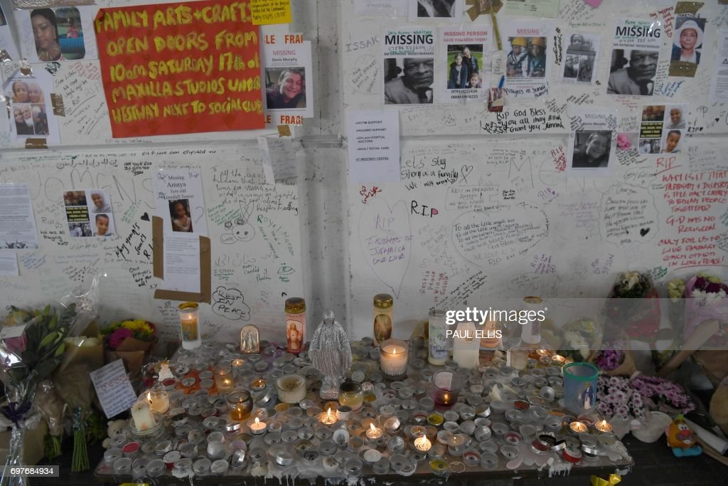 Tributes left to the victims of the Grenfell Tower fire, a residential tower block in Kensington, west London, are pictured on June 19, following the June 14 fire which gutted the residential building. Seventy-nine people are dead or missing and presumed dead following a devastating blaze in a London tower block, police said Monday, as Britain held a minute's silence for the victims. / AFP PHOTO / Paul ELLIS