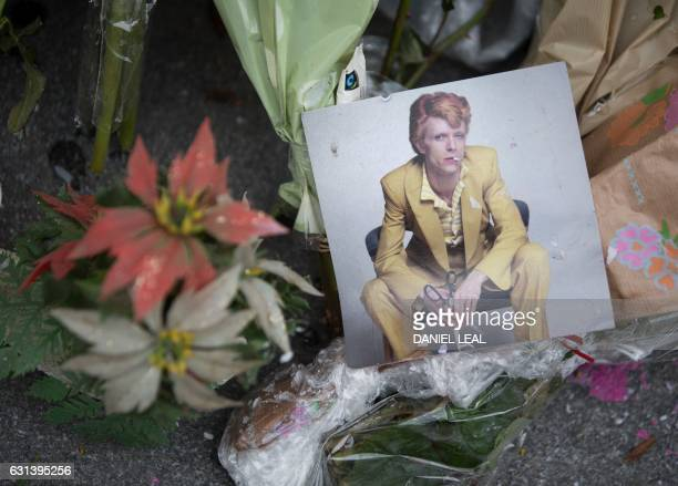 Tributes to British pop icon David Bowie are seen at the mural of the pop icon in Brixton south London on January 10 2017 on the first anniversary of...
