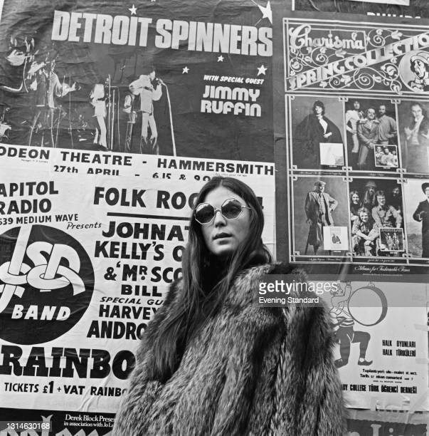 Tricia Parker-Smith poses in sunglasses and a fur coat in front of a wall of concert posters, London, UK, 6th May 1974. One poster is advertising an...