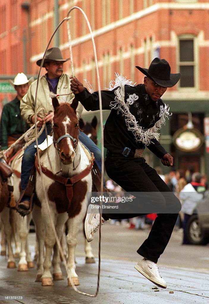 Trick roper Andre McClain does some fancy rope and foot work as he walks up 17th Street in the 2001 National Western Stock Show Parade Tuesday. : News Photo