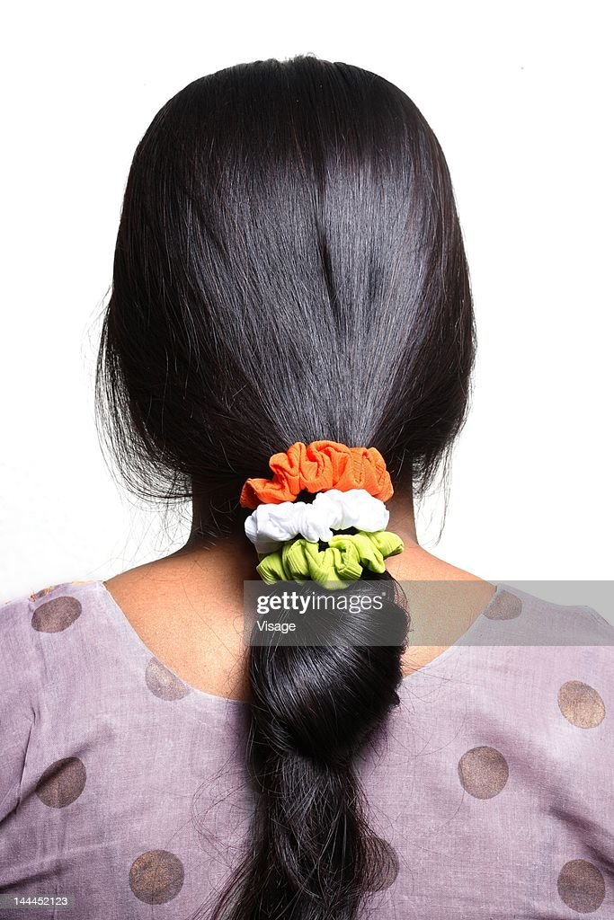 Tri-colored rubber bands on woman's hair : Stock Photo