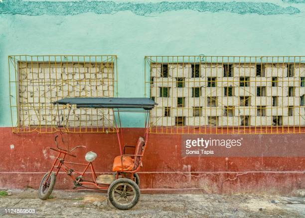 tricycle agains wall in havana cuba - old havana stock pictures, royalty-free photos & images
