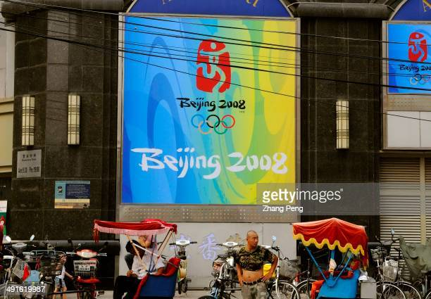 tricycles under the huge billboard of Beijing 2008 Olympic games Beijing is now prepared for the Olympic games and everywhere can be seen the slogans...