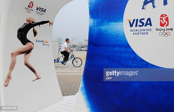 A tricyclist is seen riding past an ATM machine on the Olympic Green in Beijing on July 28 2008 Criticized by some human rights organizations in...