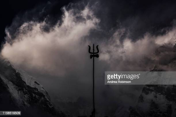 trident amidst swirling clouds and light on the mountain peaks at annapurna base camp, himalayas, nepal - hindu god stock pictures, royalty-free photos & images