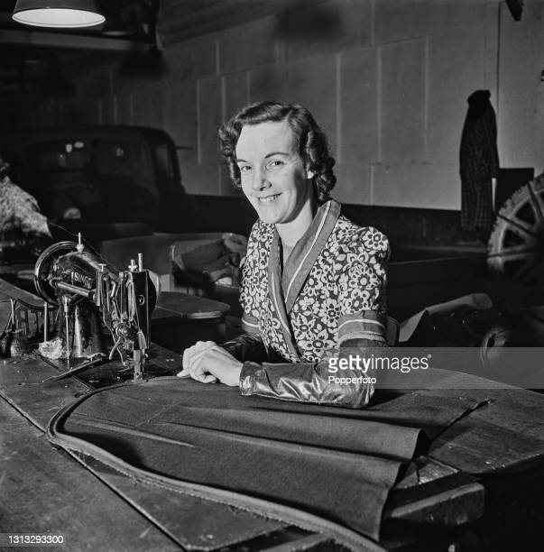 Trim shop machinist Betty Dunkley works at a Singer sewing machine at a Vauxhall Motors factory in England during World War II in February 1941.