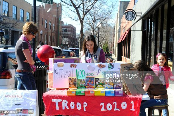 Trina Sheridan watches as her her daughters Molly age 13, and Edie age 5, sell Girl Scout cookies in Chicago on February 19, 2017. On a sunny Sunday...