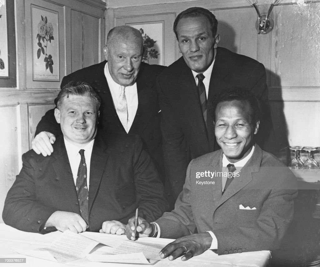 Trinbagonian boxer Percy Lewis (right) signs a fight contract at La Primavera restaurant in Frith Street, London, 19th July 1960. Looking on are (left to right) matchmaker Jack Duncan, manager Jim 'The Bishop' Wicks and boxer Henry Cooper (1934 - 2011). The Super Featherweight match between Lewis and Billy Calvert of Sheffield took place on 19th August at the Winter Gardens, Banbury, and ended in a draw.
