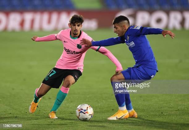 Trincao of Barcelona is challenged by Mathias Olivera of Getafe during the La Liga Santader match between Getafe CF and FC Barcelona at Coliseum...