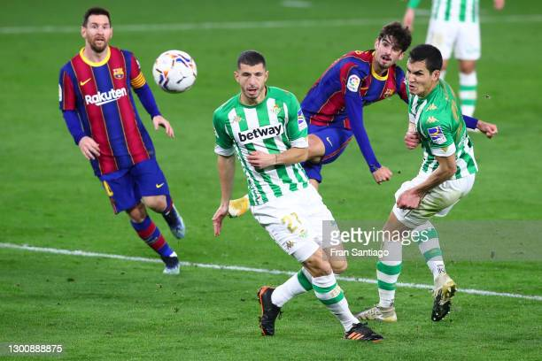 Trincao of FC Barcelona scores their team's third goal past Guido Rodriguez of Real Betis during the La Liga Santander match between Real Betis and...