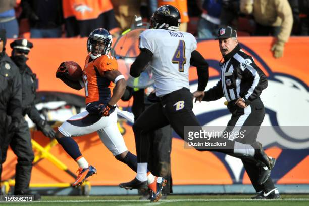 Trindon Holliday of the Denver Broncos returns a punt 90yards for a touchdown in the first quarter against Sam Koch of the Baltimore Ravens during...