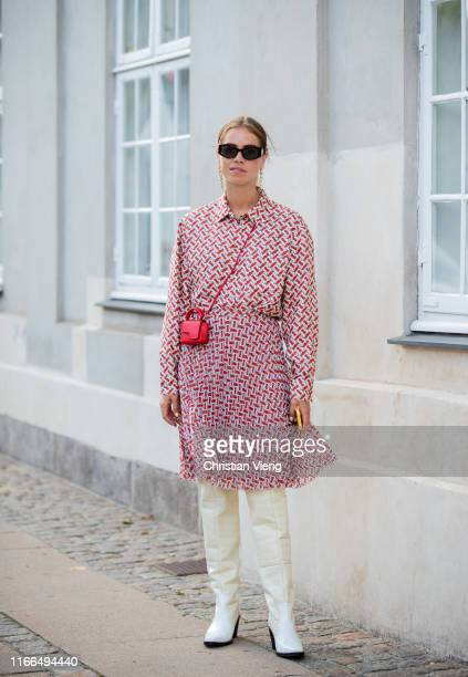 Trine Kjaer is seen wearing red white dress, red mini bag, white boots outside Mykke Hofmann during Copenhagen Fashion Week Spring/Summer 2020 on...