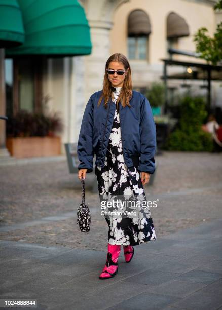 Trine Kjaer wearing navy bomber jacket black white Ganni dress Chanel bag is seen during Stockholm Runway SS19 on August 28 2018 in Stockholm Sweden