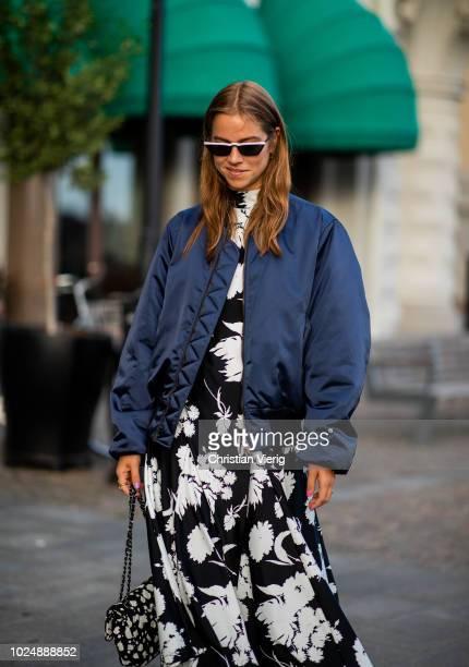 Trine Kjaer wearing navy bomber jacket black white Ganni dress Chanel bag is seen during Stockholm Runway SS19 on August 28 2018 in Stockholm Sweden