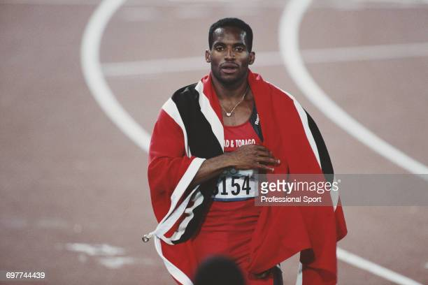Trinidad and Tobago track athlete Ato Boldon pictured wrapped in his national flag after finishing in second place to win the silver medal for...