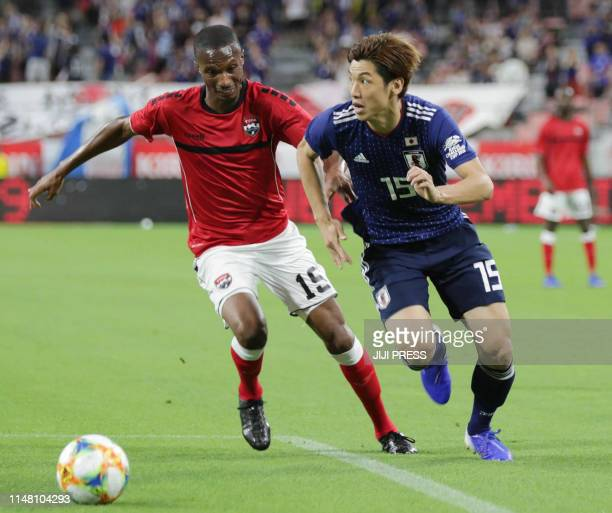 Trinidad and Tobago's midfielder Kevan George and Japan's forward Yuya Osako compete for the ball during their friendly football match at Toyota...