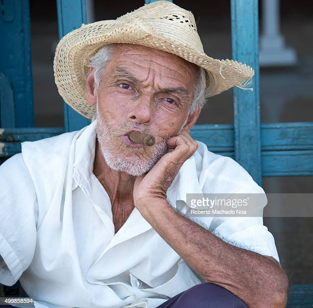Trinidad de Cuba scenes Old man holding a cigar in his mouth Cuban cigars are hailed as the best in the world for the quality of tobacco used in...