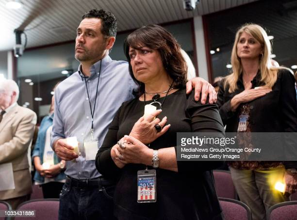 Trinidad Rios left embraces his mother Gloria during a singing of the National Anthem at the Orange County District Attorney's 9th Annual Victims'...
