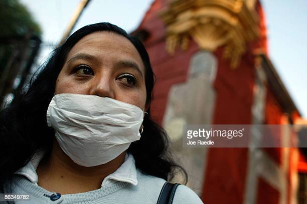 Trinidad Tirado Cardenas wears a surgical mask to help prevent contamination with the swine flu as she waits for a ride May 2 2009 in Mexico City...