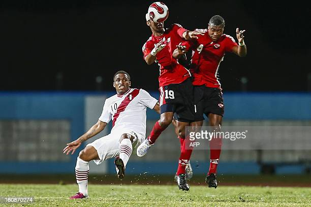 Trinidad & Tobago players Sheldon Bateau and Carlyle Mitchell try to head the ball next to Peru's Jefferson Farfan during a friendly match at Ato...