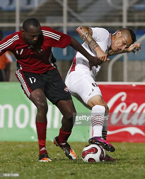 Trinidad Tobago's Daniel Cyrus and Peru's Paolo Guerrero vie for the ball during their friendly match at Ato Bolton stadium in Couva Trinidad on...